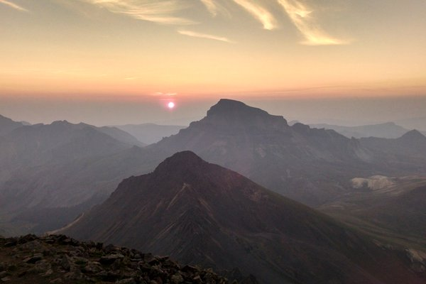 The sun begins to rise into a hazy sky behind Uncompahgre Peak, seen from Wetterhorn Peak